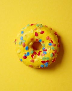 Ring doughnut with sprinkles and yellow glazing, on a yellow backgroun